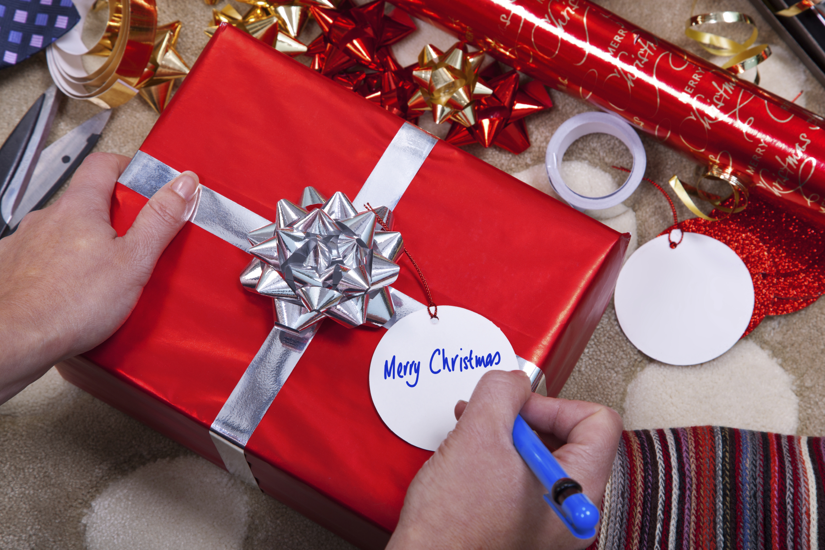 Photo of a woman writing Merry Christmas on a gift tag on a red present with silver ribbon and bow. Of course you could easily add your your message.