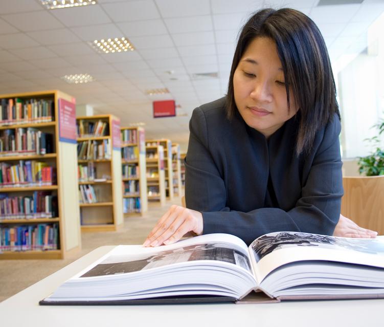 Mädchen liest Abizeitung in Bibliothek