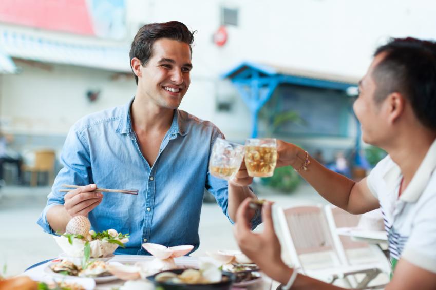Zwei Männer, die sich während dem Essen unterhalten.