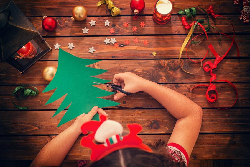 Beim Weihnachtsbasteln - kleines Mädchen schneidet für eine kreative Karte einen Weihnachtsbaum aus Papier aus. ier aus für eine