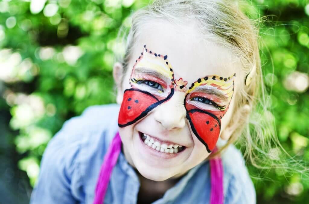 Mädchen mit geschminktem Gesicht beim Karneval