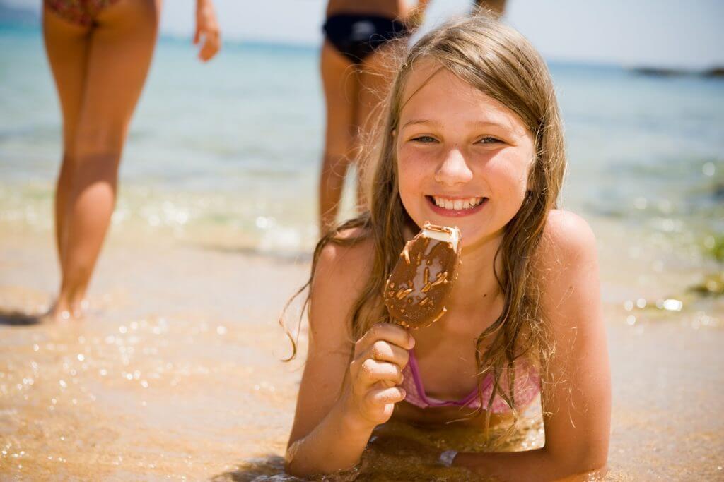 Ein Mädchen isst Eis am Strand - kalenderblatt für den August