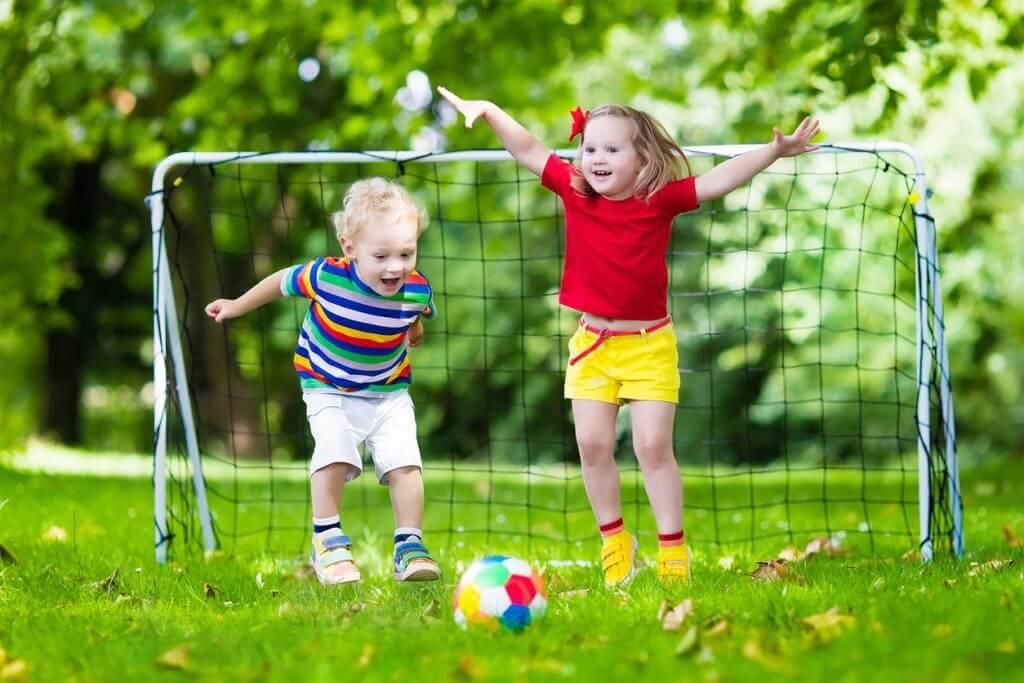 Kinder spielen Fußball im Sommer - Kalenderblatt für den Juni