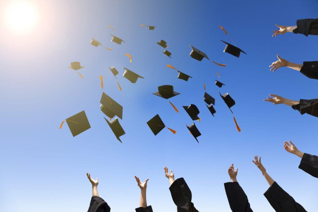 Bachelorabsolventen werfen Ihre Hüte in die Luft