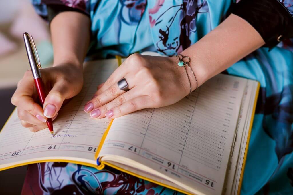 Eine Frau schreibt in den Terminkalender.