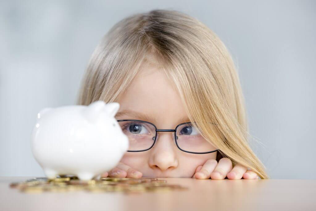 Kind mit Brille schaut auf Sparschwein