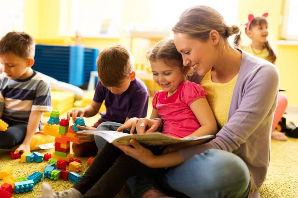 Kinmdergaertnertin mit Kind und Buch