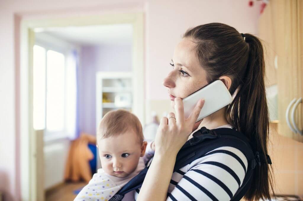 Beschaeftigte Mutter telefoniert mit Kind im Arm