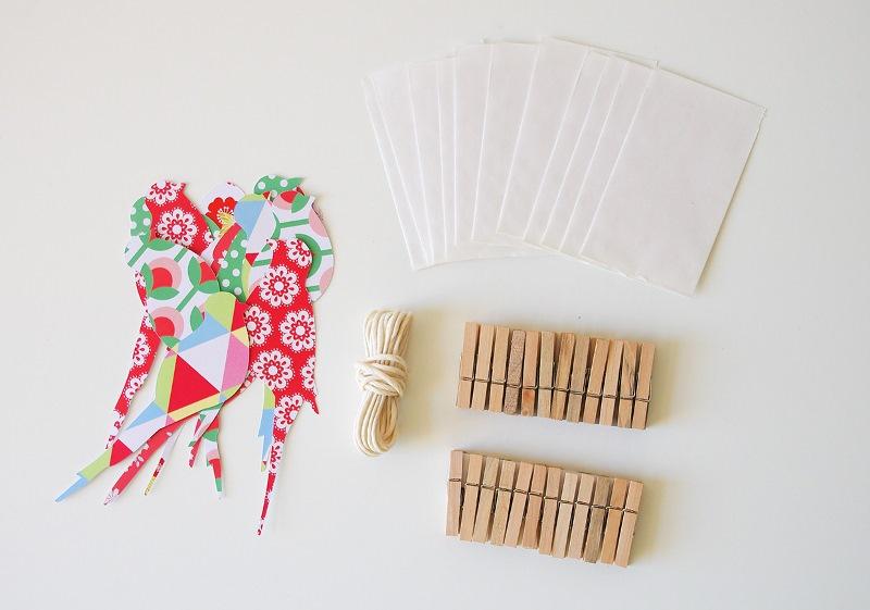 Papiervögel, Wäscheklammern und Papiertütchen als Bastelmaterial für einen Vogel-Adventskalender